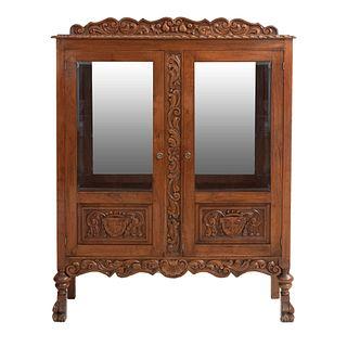 Vitrina. SXX. Estilo Colonial Español. En talla de madera. Con 2 puertas abatibles y laterales con cristal y espejo interno. 163 x 126