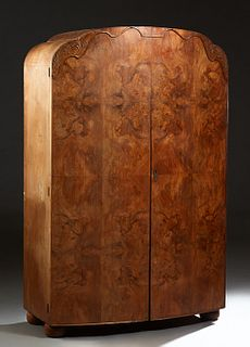 English Art Deco Carved Walnut Double Door Armoire, c. 1940, the arched serpentine top over two highly figured doors, on large bun feet, the interior