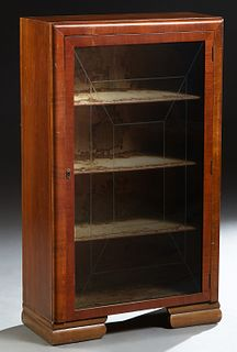 English Art Deco Carved Mahogany Bookcase, c. 1940, the rectangular top over a single glazed door with interior geometric incised decoration, on stepp