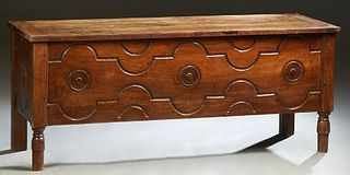 French Provincial Carved Walnut Coffer, 19th c., the three board hinged top over an incised and relief carved front and sides, on turned tapered cylin