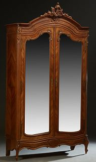 French Carved Mahogany Louis XV Style Armoire, early 20th c., the arched crown with a central pierce C-scroll Crest, over double beveled mirror doors,