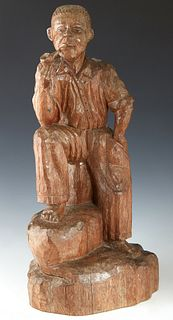 American Folk Art Carved Wooden Figure, 19th c., of a seated Afro-American man smoking a pipe, carved from a single log, H.- 22 in., W.- 10 1/2 in., D