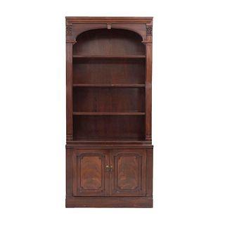 Librero. Siglo XX. Elaborado en madera. A dos cuerpos. Con 3 entrepaños, 2 puertas abatibles inferiores y soporte tipo zócalo.