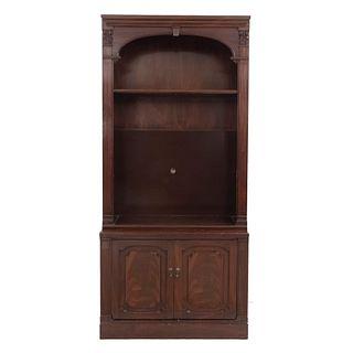 Librero. Siglo XX. Elaborado en madera. A dos niveles. Con 3 entrepaños, 2 puertas abatibles inferiores y soporte tipo zócalo.