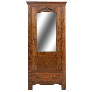 Ropero. Siglo XX. Elaborado en madera. Con cajón inferior, puerta con espejo biselado y soportes lisos.
