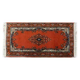 Tapete para pie de cama. Siglo XX. Estilo mashad. Elaborado en fibras de lana y algodón. Decorado con medallón central.