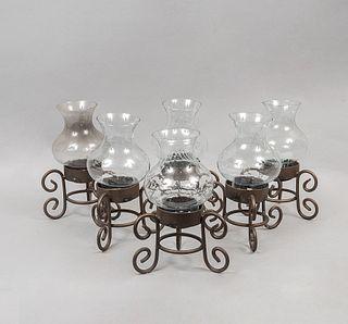 Lote de 6 candeleros. Siglo XX. Elaborados en metal. Con pantallas de vidrio y soportes tipo roleo.