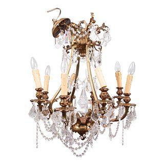 Candil. SXX. En metal dorado. Para 8 luces. Con arandelas florales y brazos semicurvos. Decorado con cuentas y almendrones de cristal.