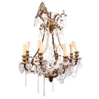Candil. Siglo XX. En metal dorado. Para 8 luces. Con arandelas florales y brazos semicurvos. Decorado cuentas y almendrones de cristal.