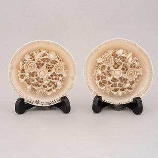 Lote de 2 platos decorativos. China. Siglo XX. En talla de marfil. Con portaplatos de madera barnizada.