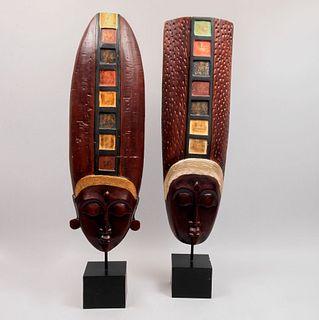 Lote de 2 máscaras tribales. Siglo XXI. En talla de madera. Con tocados casetonados detallados con policromía.