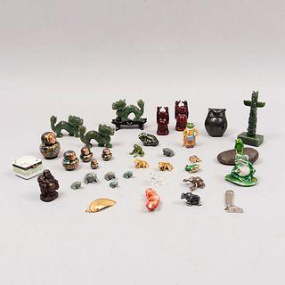 Lote de 28 piezas. China, Rusia y otros, siglo XX. Tallas en coral, serpentina, metal, cerámica, pasta, resina, madera y otros.