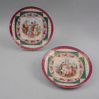 Par de platos decorativos. Elaborados en porcelana Prov. Sate. Decorados con escenas neoclásicas y motivos en esmalte dorado.Pz:2