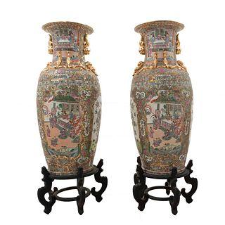 Par de jarrones. China. Principios siglo XX. Estilo Familia Rosa. Elaborados en porcelana policromada. Con bases de madera.