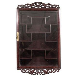 GABINETE. CHINA, SIGLO XX. Madera tallada. Puerta frontal con cubierta de vidrio y remates a manera de volutas. 77 x 47 x 12.5 cm