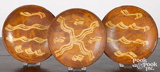 Three slip decorated redware plates, 19th c.