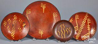 Four Pennsylvania slip decorated redware plates