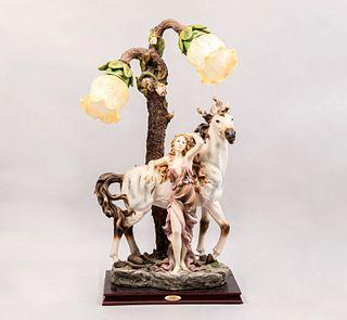 Lámpara de mesa con figura de amazona. Siglo XX. De la marca Rubg's Collection. Elaborada en resina y pantallas de vidrio.