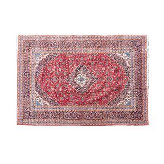 Tapete. Siglo XX. Estilo Kirman. Anudado a mano en fibras de lana y algodón. Decorado con elementos vegetales y florales.