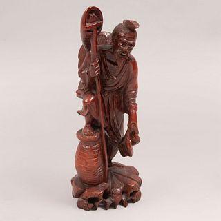 Pescador. Origen oriental. Siglo XX. En talla de madera entintada. Con aplicaciones de pasta en ojos y boca. 31 cm de altura