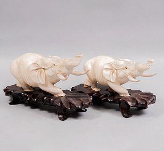 Lote de 2 elefantes. China, siglo XX. Tallas en marfil con detalles en tinta negra adheridos a bases de madera.