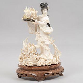 Quan Yin con flor de loto. China, siglo XX. Talla en marfil con detalles en tinta negra y base de madera. 17 cm de altura