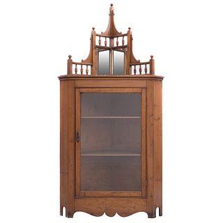 Vitrina esquinera. Siglo XX. Elaborada en madera tallada. Puerta abatible con vidrio, remate con dos espejos de lunas rectangulares.