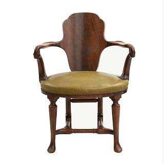 Sillón. Siglo XX. Estructura de madera. Con respaldo cerrado, asiento de piel, chambrana en caja y soportes tipo jarrón.