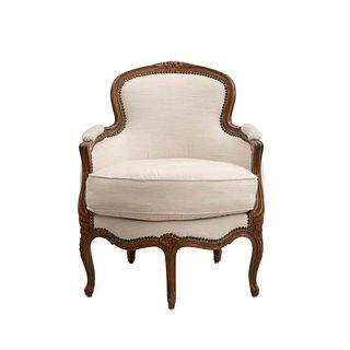 Sillón. Siglo XX. Estructura de madera, con tapicería textil color beige. Respaldo cerrado, asiento acojinado.