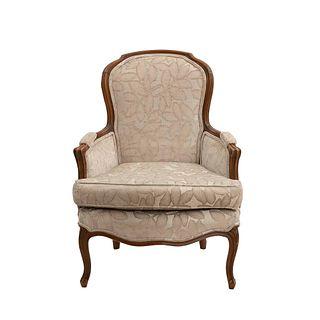 Sillón. Siglo XX. Estructura de madera, con tapicería textil color beige. Respaldo cerrado, asiento acojinado, fustes semicurvos.