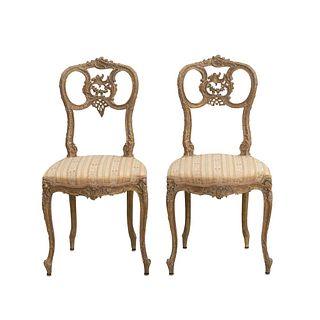 Par de sillas. Siglo XX. Estilo Luis XVI. Elaboradas en madera tallada. Con respaldos semi abiertos.
