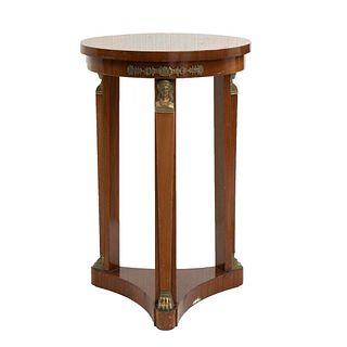 Mesa consola. Siglo XX. En talla de madera. Con cubierta circular, fustes tipo estípite y soporte a manera de entrepaño.