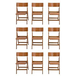Juego de 9 sillas. Siglo XX. Diseño plegable Elaboradas en madera. Con respaldos semi abiertos, fustes y soportes lisos.