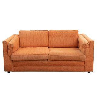 Loveseat. Siglo XX. En tapicería color anaranjado. Con respaldos, asientos y laterales acojinados.