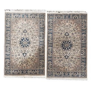 Par de tapetes para pie de cama. Siglo XX. Estilo mashad. Elaborados en fibras sintéticas. Decorados con medallones centrales.