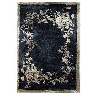 Tapete. Siglo XX. Elaborado en fibras sintéticas. Decorado con motivos vegetales y florales sobre fondo negro. 180 x 122 cm.
