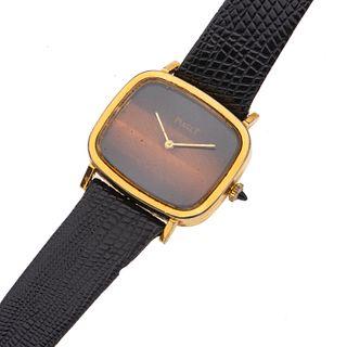 Reloj Piaget. Movimiento manual. Caja rectangular en acero dorado. Carátula con esmalte. Correa de piel. Estuche.