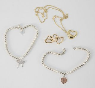 Tiffany & Company Four Piece Lot, to include two 14 karat gold hearts, 8.3 grams; one pin with triple heart; one heart on chain; along with two sterli