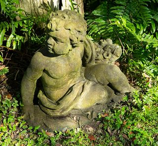 A Pair of Cast Stone Seated Putti Height 21 1/2 x width 24 x depth 10 inches.