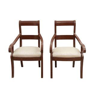 Par de sillones. Siglo XX. Elaborados en madera. Con respaldos semi abiertos, asientos en tapicería color beige.