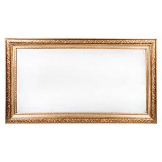 Espejo. Siglo XX. Elaborada en madera dorada. Con luna rectangular biselada. Decorado con elementos florales y vegetales. 78 x 138 cm