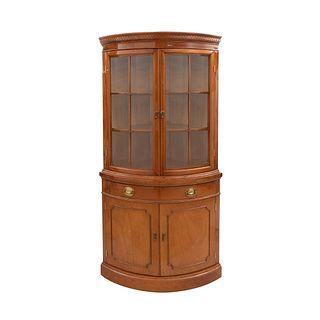 Esquinero. Siglo XX. Elaborado en madera. Con 4 puertas abatibles, dos con vidrio, cajón central y soporte tipo zócalo.