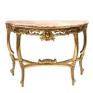 Mesa consola. Siglo XX. Estilo Luis XV. Elaborada en madera dorada. Con cubierta irregular de mármol beige jaspeado. 115 x 82 x 45 cm