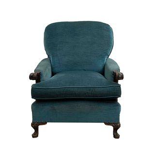 Sillón. Siglo XX. Estructura de madera, con tapicería textil color azul. Respaldo cerrado, asiento acojinado.