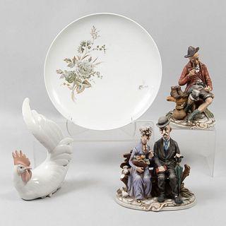 Lote de 4 piezas. Alemania, España y Japón. SXX En porcelana, una de Bavaria. Consta de: platón, vagabundo, gallo, otra.
