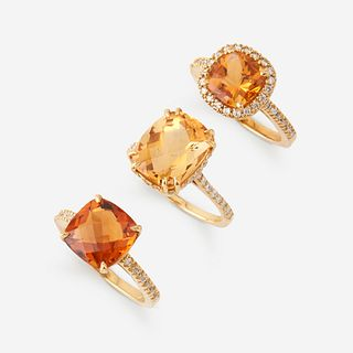 A collection of three citrine, diamond, and eighteen karat gold rings,