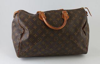 Louis Vuitton Brown Monogram Coated Canvas 35 Speedy Handbag, with golden brass hardware, opening to a light brown canvas lined interior with a small