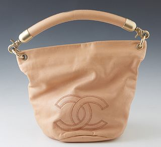 Chanel Nude Leather Bucket Bag, c. 2003-2004, the exterior with stitched Chanel logo and frosted gold metal accents, the metal Chanel pull zipper open