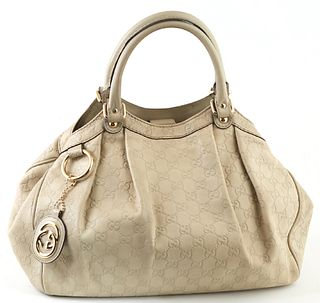 Gucci Ivory Guccissima Leather PM Sukey Handbag, with a golden brass key ring and Gucci logo charm, the magnetic clasp opening to a large print interi