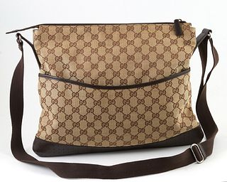 Gucci Monogrammed Canvas Large Messenger Bag, with a perforated brown calf leather bottom and front snap close pocket, the interior of the bag lined w